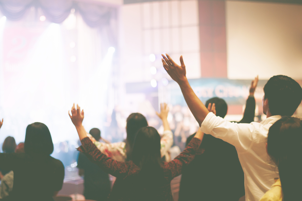 churchgoers raise hands in service