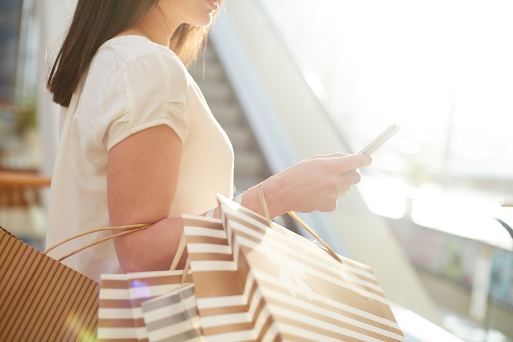 Shopper with paper bags messaging after shopping