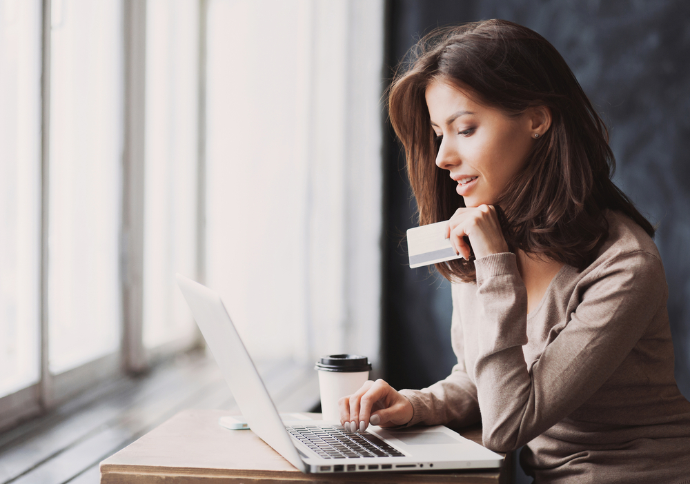 Young woman holding credit card and using laptop computer