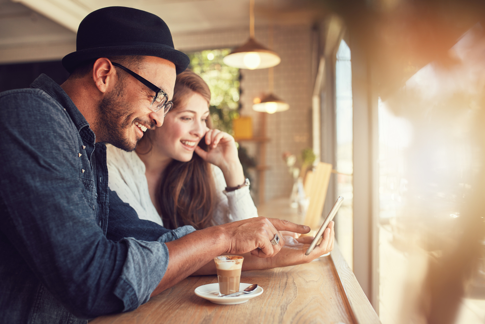 Couple smiling looking at phone