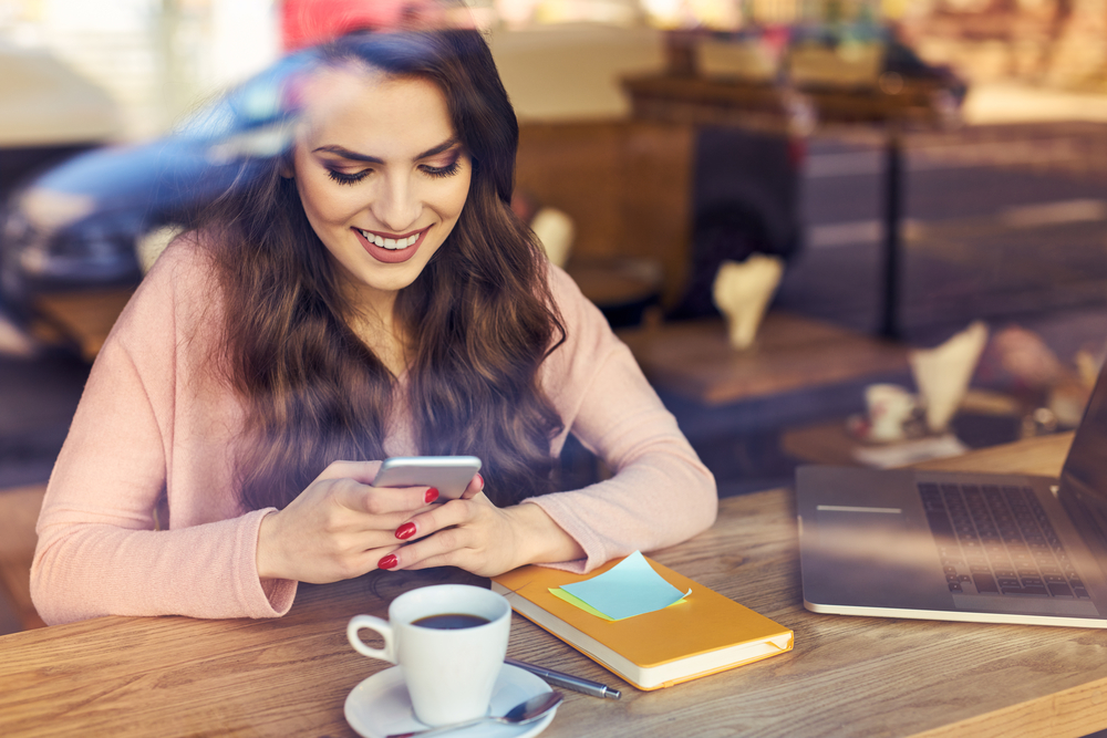 Women receiving message smiling at phone