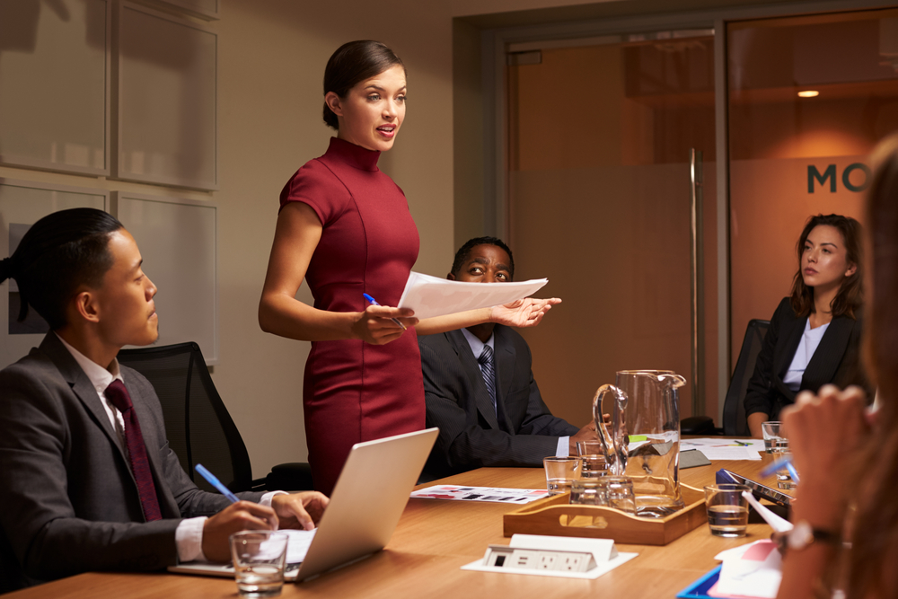 Female Boss presents to group of employees
